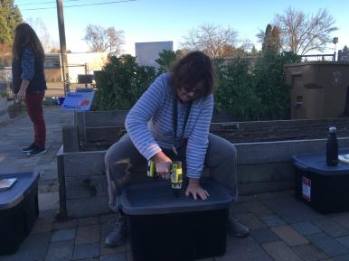 Arlene Bates, of the School Garden Task Force, drills holes in a worm bin.